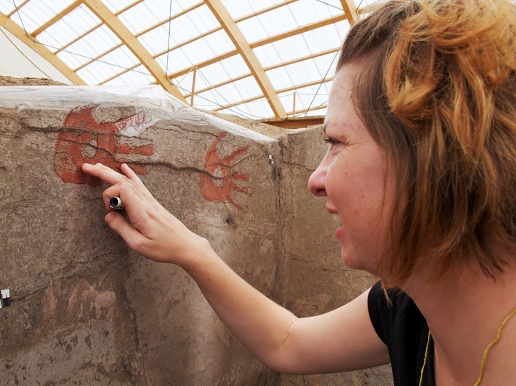 Photo of Kathryn tracing Neolithic handprints. Photo by Jason Quinlan